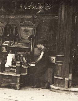 BOOTBLACK, 1910. A young bootblack working on Canal Street in New York City