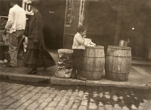 BOSTON: SLUMS, 1909. Young boy eating scraps out of trash bins in a Boston slum