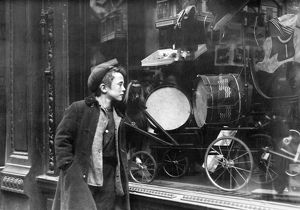 A boy looking at Christmas toys in a shop window. Photograph, early 20th century.