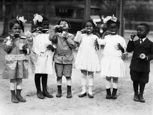 BRUSHING TEETH, c1910. First graders brushing their teeth outside of school in Washington