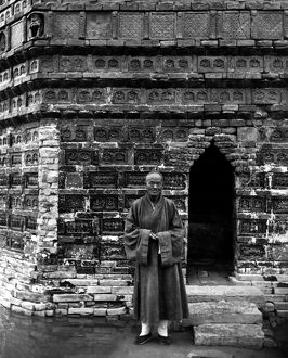 A Buddhist monk standing outside the entrance of the Iron Pagoda, built in the mid-11th century