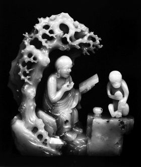 Carved jade figure of a lohan and a monkey in a grotto. Ching Dynasty, late 17th century.
