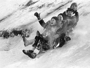 Children tobogganing down a hill in Canada. Photograph, late 20th century.