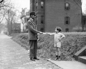 CHRISTMAS, 1920. A boy handing a mail carrier a letter for Santa Claus. Photograph