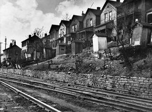CINCINNATI: HOUSES, 1935. A row of low-income houses with outhouses facing railroad tracks