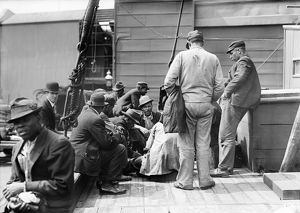 COAL PASSERS, 1911. Coal passers discussing a strike on the deck of a ship. Photograph