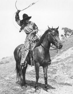 COWGIRL, c1920. Josie Sedgwick showing the use of a lariat. Photograph, c1920.