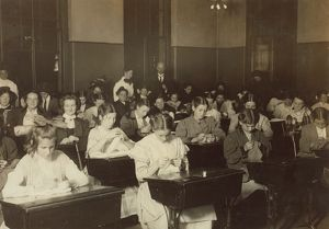 DRESSMAKING CLASS, 1909. Working girls learning dressmaking in a free evening class