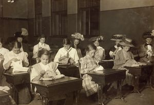 EMBROIDERY CLASS, 1909. Working girls learning embroidery in a free evening class