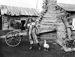 ENTERTAINER, 1901. An entertainer and a goose in a display of log cabins at the