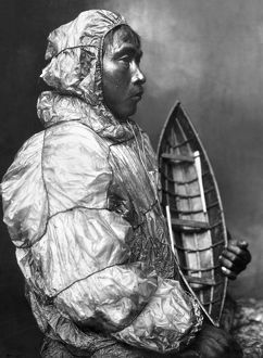 An Eskimo kayaker wearing a waterproof jacket and holding a toy boat he made for his son. Photgraphed by the Lomen Brothers, early 20th century.