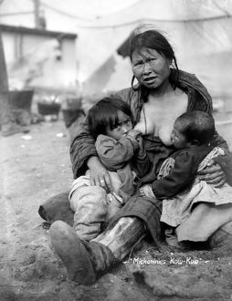 ESKIMO MOTHER AND BABIES. An Inuit mother breast-feeding her two babies, North America