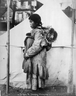 ESKIMO WOMAN AND CHILD. An Eskimo woman carrying a baby on her back, Arctic region