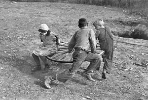 Farm children playing on a homemade merry-go-round. Photograph, 1937, by Russell Lee.