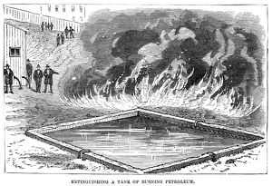 FIREFIGHTING, 1876. Demonstration of extinguising a tank of burning petroleum, at