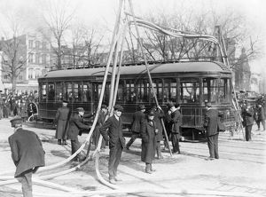 FIREMEN, c1918. Firemen with hoses over a street car, United States. Photograph, c1918