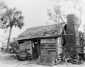 FLORIDA: LOG CABIN. An African American man standing in the doorway of a log cabin