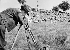 A geologist (foreground) searches for an oil deposit in an American field with the