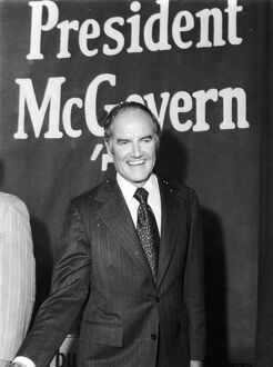 GEORGE McGOVERN (1922- ). American politician. Senator McGovern beneath a poster in New York City