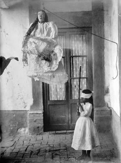 A girl swings at a Christmas piñata in Mexico, c1915.