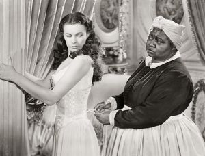 GONE WITH THE WIND, 1939. Hattie McDaniel assists Vivien Leigh while offering some