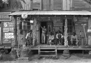 A group of African American men sitting on the porch of a country store, with the