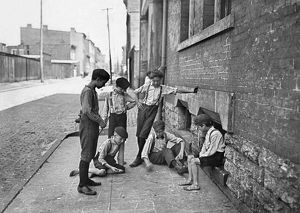 Group of boys gambling with dice on the sidewalk of Cincinnati, Ohio. Photograph by Lewis Hine, c1908.