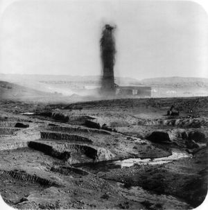 Gushing oil well and a stream of oil in the foreground, Kirkuk, Iraq, 1932-33.