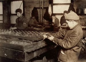 HINE: CHILD LABOR, 1917. Boys linking bedsprings in a mattress factory in Boston