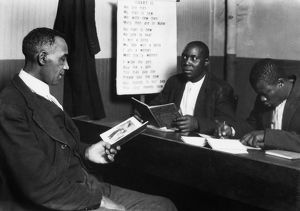 HINE: EDUCATION, 1920. Three African-American men reading and writing, somewhere