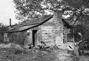 HINE: LOG CABIN, 1921. A small run-down log cabin occupied by a family that has