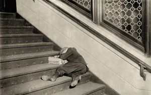 HINE: NEWSBOY, 1912. Newsboy sleeping on the stairs with newspapers at night in Jersey