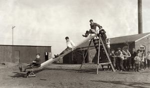 HINE: SCHOOLYARD, 1917. Children playing on the slide in the schoolyard of the