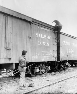 HOBOS, c1915. A hobo climbing on top of a railroad car. Photograph, c1915
