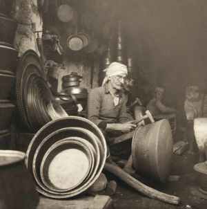 ISRAEL: METAL WORKERS, 1938. Coppersmith at Nazareth, Israel, hammering out a 'dist