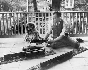 John N. Swartzell and his daughter, Margaret, playing with an electric train on the