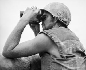 KOREAN WAR: BUNKER HILL. A Marine observes the results of artillery action during