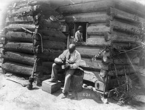 LOG CABIN, c1895. An African American man seated on a tree stump, outside a log