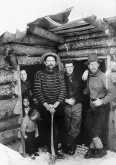 LOG CABIN, c1903. Three men, a woman and four children standing in the doorway of