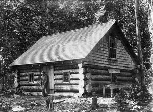 MAINE: LOG CABIN. A man standing in front of a log cabin at the Lucky Camp in Spencer Bay