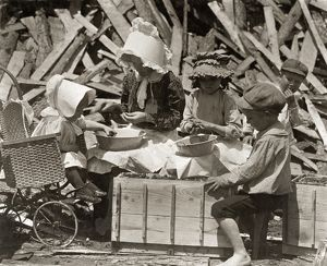 MIGRANT WORKERS, 1910. Mother and children hulling strawberries for two cents a