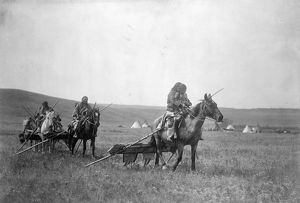 MOVING CAMP, c1908. Gros Ventre people moving camp with horses and travois in Montana