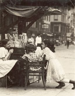 NEWSPAPER VENDORS, 1910. Three young girls working at a newspaper stand on Canal