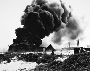 Oil tanks burn after being attacked by Japanese warplanes at the U