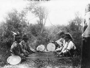 OJIBWA GAME, c1910. Four Ojibwa Native American men playing a moccasin game, in