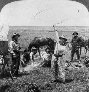 OKLAHOMA: COWBOYS, c1905. A cowboy twirling a lariat in the air as six other cowboys