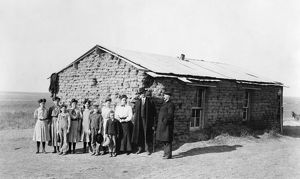 ONE-ROOM SCHOOLHOUSE, 1908. Children posing outside of a one-room sod schoolhouse