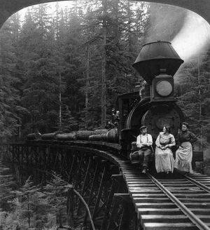 OREGON: LOGGING TRAIN. Two women and a man seated on front of logging train pulling