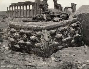 PALMYRA: RUINS. Man sleeping on a sculpted capital in front of ruins of a colonnade at Palmyra