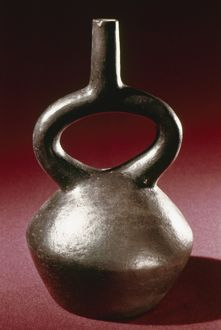 PERU: CHIMU JAR. Polished blackware stirrup jar, made by the Chimu culture of ancient Peru